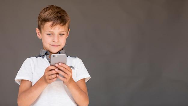 Jongen die een spel op de telefoon met exemplaarruimte speelt Gratis Foto