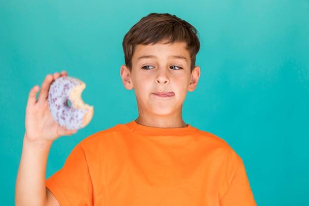 Jongen die heerlijke verglaasde doughnut bekijkt Gratis Foto