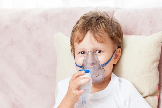 Jongen die inhalatie met een verstuiver thuis maakt Premium Foto