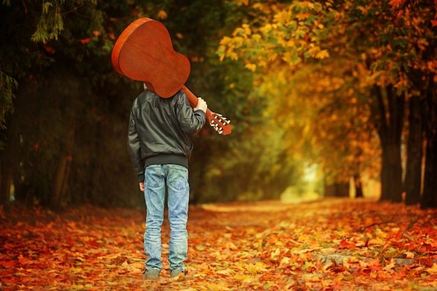 Jongen die met gitaar op de de herfstweg loopt. achteraanzicht Premium Foto