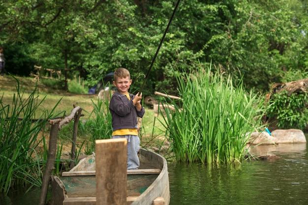 Jongen die met hengel in een houten boot vist Gratis Foto