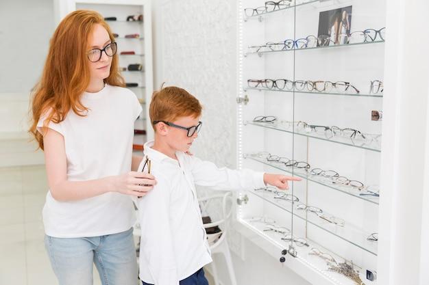 Jongen die op oogglazen richt terwijl status met vrouwelijke opticien in optica Gratis Foto