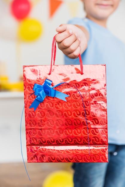 Jongen die rode zak met blauwe verfraaide boog toont Gratis Foto