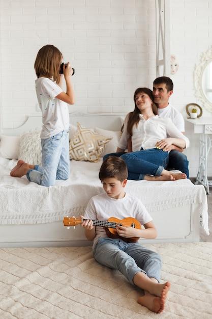 Jongen die ukelele speelt voor zijn zus die een foto van hun ouders neemt Gratis Foto