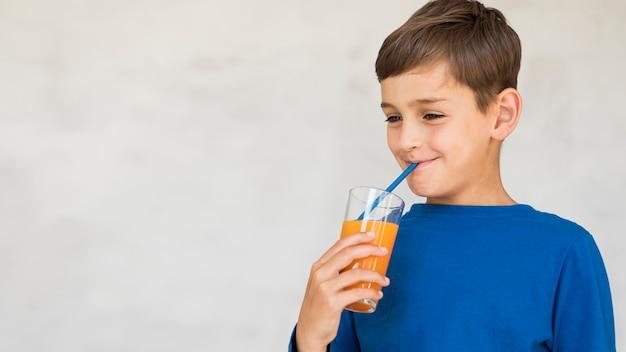 Jongen die van zijn jus d'orange met exemplaarruimte geniet Gratis Foto