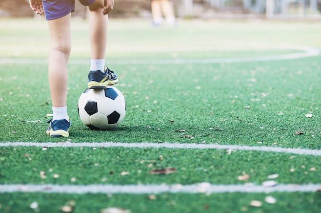Jongen die zich met bal op voetbalgebied klaar om te beginnen of nieuw spel speelt te bevinden Gratis Foto
