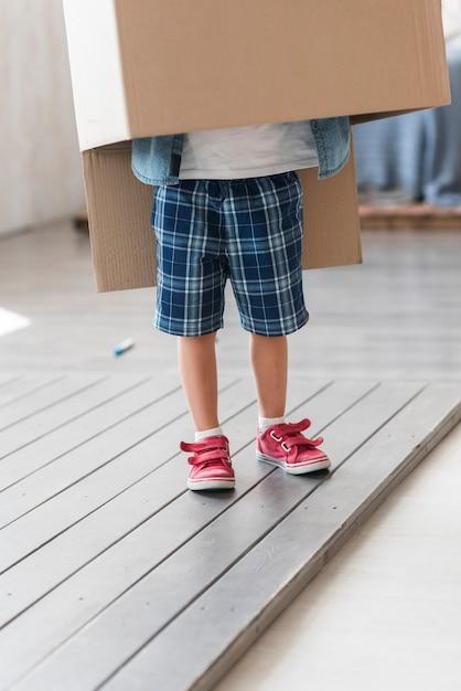 Jongen die zich onder de kartondoos op plankenvloer bevindt Gratis Foto