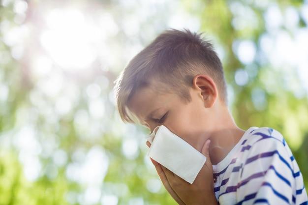 Jongen die zijn neus afveegt terwijl niest Premium Foto