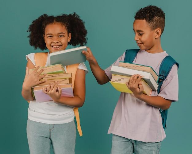Jongen die zijn vriend helpt met de boeken Gratis Foto