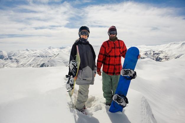 Jongen en een meisje in skibril staan op de sneeuw met snowboards Premium Foto