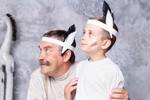 Jongen en grootvader spelen indianen op een grijze muurmuur. senior man en kleinzoon spelen injun. portret close-up Premium Foto