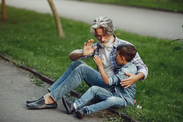 Jongen en grootvader wandelen in het park. oude man speelt met kleinzoon. familie zittend op een gras. Gratis Foto