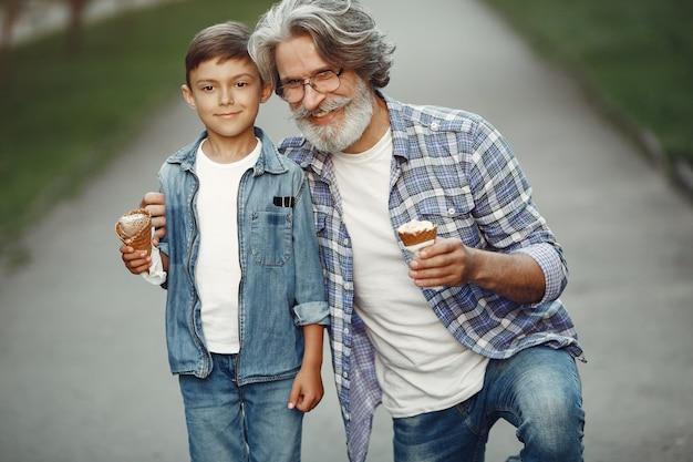 Jongen en grootvader wandelen in het park. oude man speelt met kleinzoon. gezin met ijs. Gratis Foto