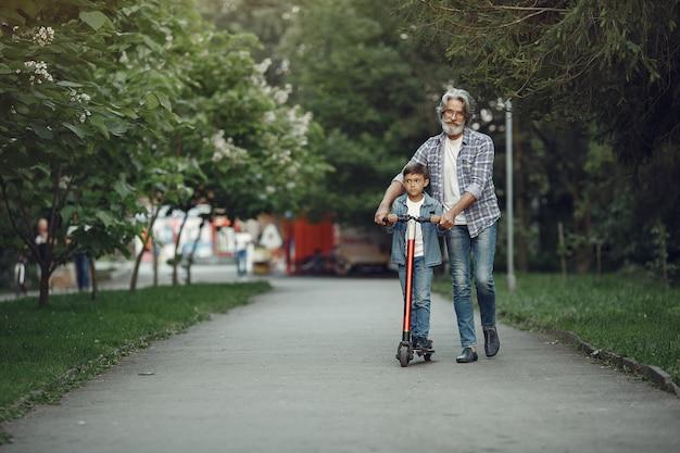 Jongen en grootvader wandelen in het park. oude man speelt met kleinzoon. kind met scooter. Gratis Foto