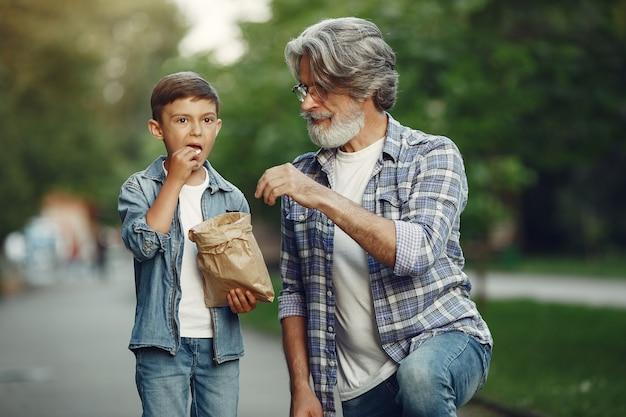 Jongen en grootvader wandelen in het park. oude man speelt met kleinzoon. mensen eten popcorn. Gratis Foto