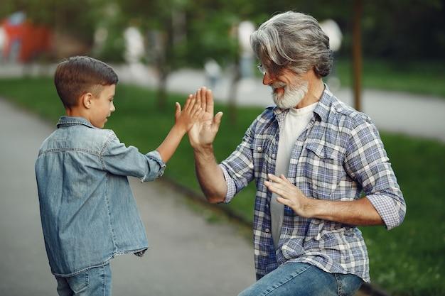 Jongen en grootvader wandelen in het park. oude man speelt met kleinzoon. Gratis Foto