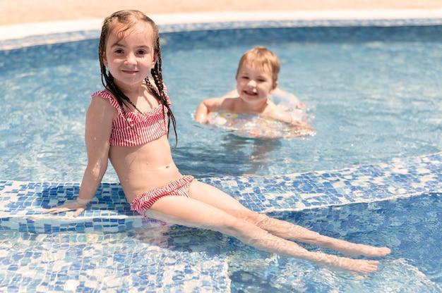 Jongen en meisje bij het zwembad Gratis Foto