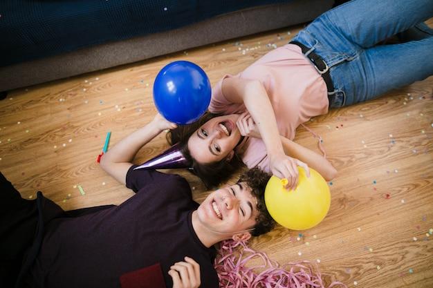 Jongen en meisje die op de vloer met ballons leggen Gratis Foto