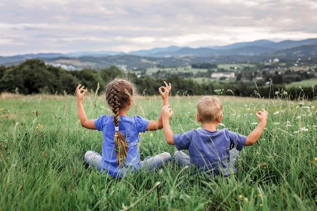 Jongen en meisje doen de ochtendoefeningen op de top van de bergen Premium Foto