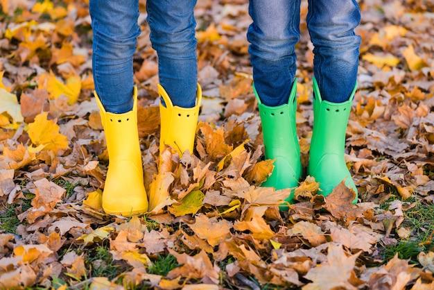 Jongen en meisje in gele en groene schoenen in de herfst Premium Foto
