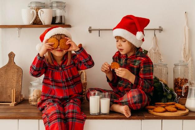 Jongen en meisje kerstmiskoekjes eten en consumptiemelk Gratis Foto