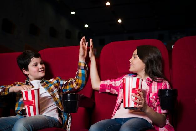 Jongen en meisje kijken naar film in de bioscoop Gratis Foto