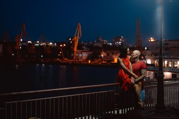 Jongen en meisje knuffelen elkaar op een achtergrond van de nachthaven Gratis Foto