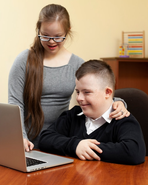 Jongen en meisje met het syndroom van down kijken naar laptop Gratis Foto
