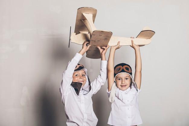 Jongen en meisje met houten modelvliegtuig en een pet met pet Premium Foto