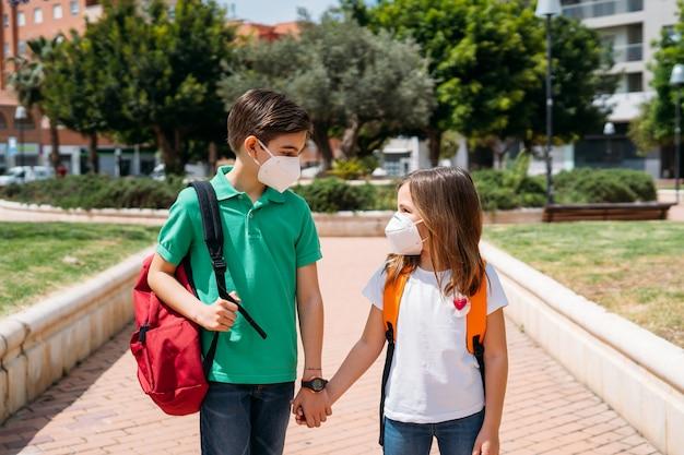 Jongen en meisje met rugzakken en maskers die naar school gaan in pandemie van het coronavirus Premium Foto