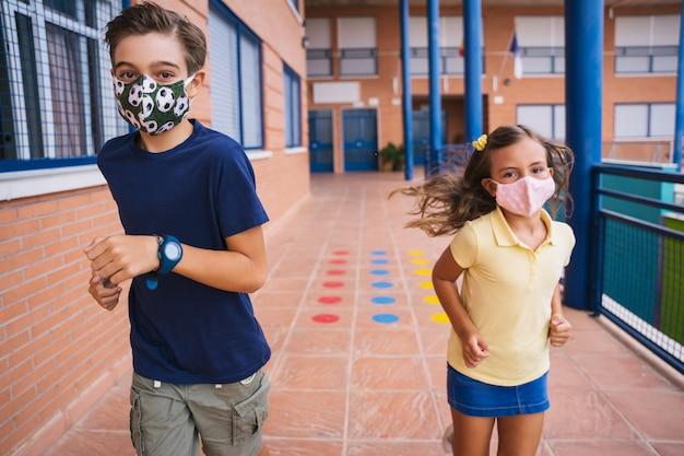 Jongen en meisje rennen op het schoolplein met gezichtsmasker tijdens covid pandemie. terug naar school tijdens de covid-pandemie Premium Foto