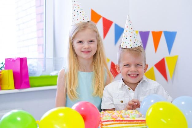 Jongen en meisje van twee blonde het kaukasische jonge geitjes in verjaardagshoeden die camera bekijken en bij verjaardagspartij glimlachen. kleurrijke achtergrond met ballonnen en verjaardag regenboogcake. Premium Foto