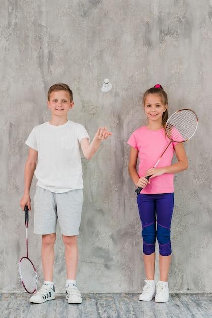 Jongen en meisjesspelers met rackets en shuttle tegen concrete achtergrond Gratis Foto