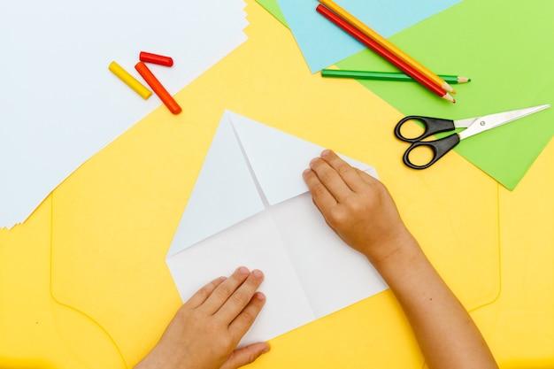 Jongen handen doet papier vliegen vliegtuig op gele tafel Premium Foto
