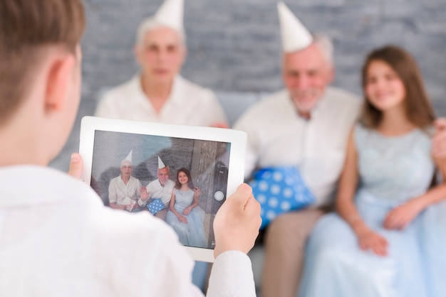 Jongen het klikken familiefoto door digitale tablet thuis Gratis Foto