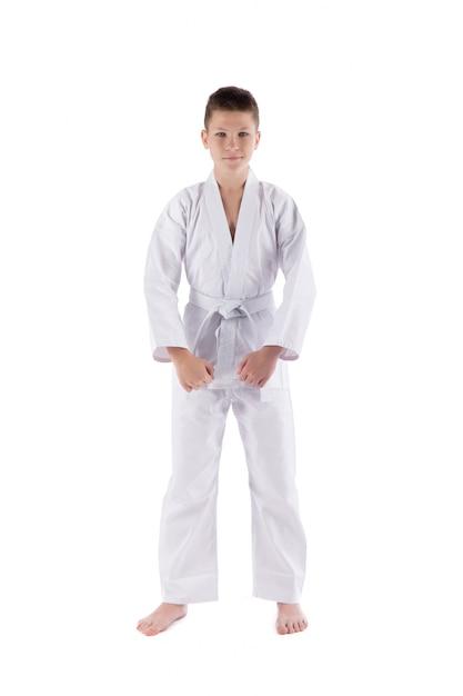 Jongen het stellen met karatetechnieken in studio op geïsoleerd wit Premium Foto