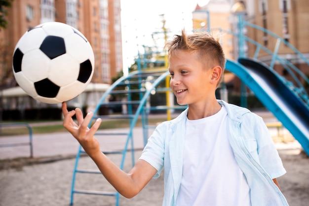 Jongen houdt van voetbal op een vinger Gratis Foto