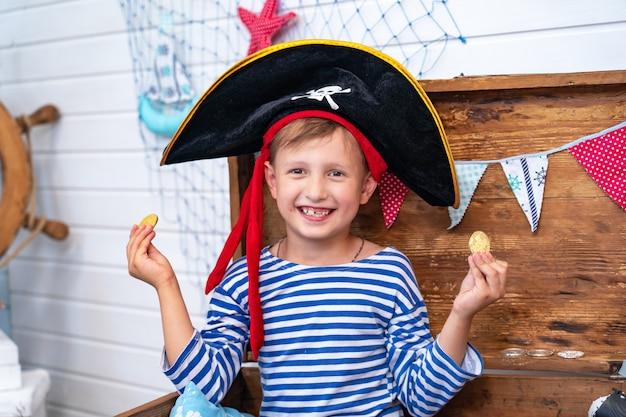 Jongen in de vorm van piraten aan het roer. vakantie decoratie piraat stijl Premium Foto