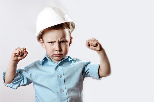 Jongen in een licht shirt en helmbouwer laat zien hoe hij sterk en zelfverzekerd is Premium Foto
