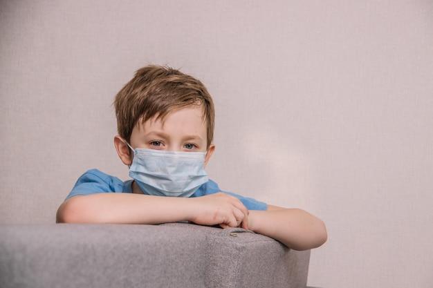 Jongen in een medisch masker zit op een bank en is verdrietig Premium Foto