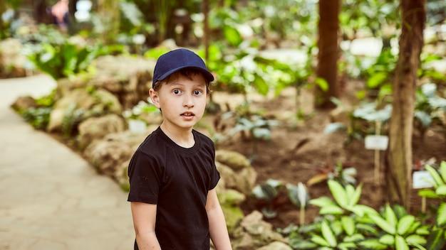 Jongen in een pet in de zomer buiten in het park Premium Foto