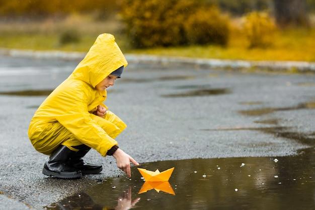 Jongen in gele waterdichte mantel en zwarte rubberen laarzen spelen met papieren handgemaakte boot speelgoed in een plas buiten in de regen in de herfst. Premium Foto
