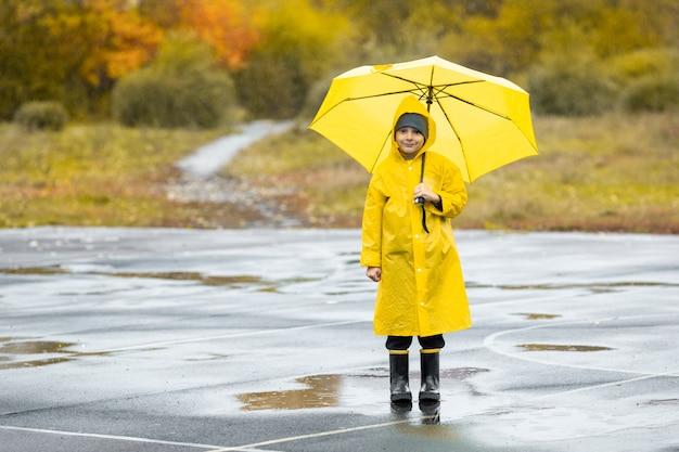 Jongen in gele waterdichte mantel en zwarte rubberen laarzen staan in een plas buiten in de regen in de herfst. Premium Foto