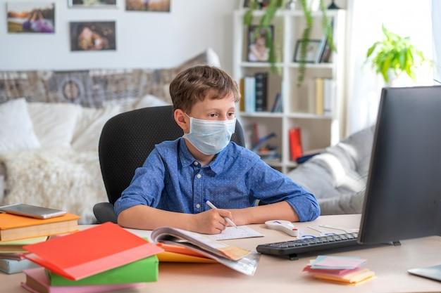 Jongen in gezichtsmasker met behulp van computer, huiswerk tijdens coronavirus quarantaine Premium Foto