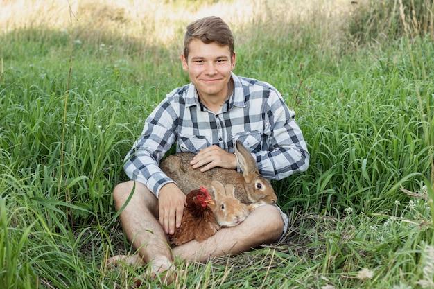 Jongen in gras het spelen met konijnen en kip Gratis Foto