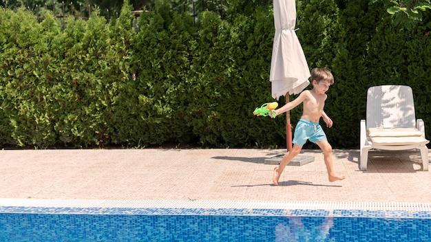 Jongen in pool het spelen met waterkanon Gratis Foto