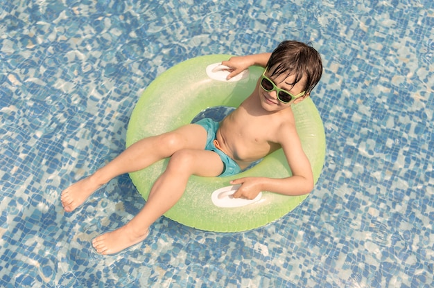 Jongen in zweven bij zwembad Gratis Foto