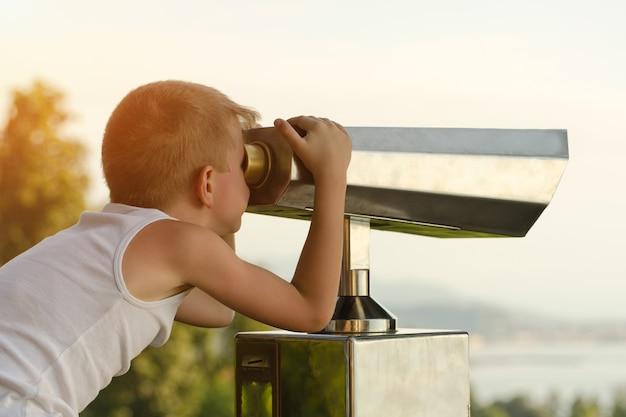 Jongen kijkt naar de grote verrekijker. Premium Foto