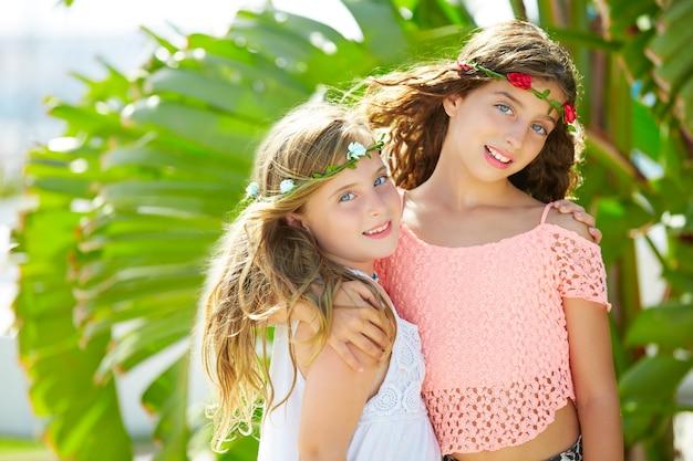 Jongen meisje zussen knuffel bananenboom bladeren heldere dag Premium Foto