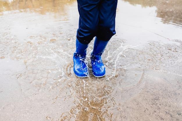 Jongen met blauwe water laarzen sprongen in een plas. Premium Foto
